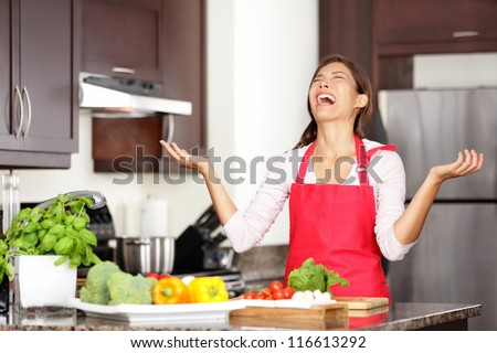 Funny cooking image of woman crying and screaming in kitchen giving up making food after unsuccessful cooking attempt. Beautiful young mixed-race Asian Chinese / Caucasian woman in kitchen. - stock photo