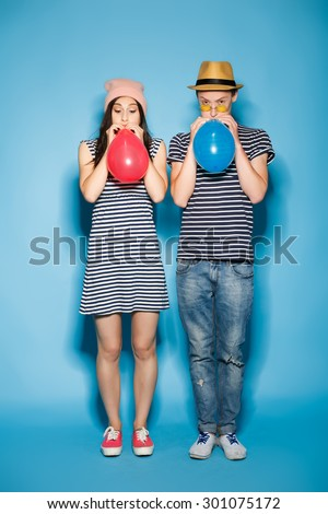 funny couple in love with balls in the studio - stock photo
