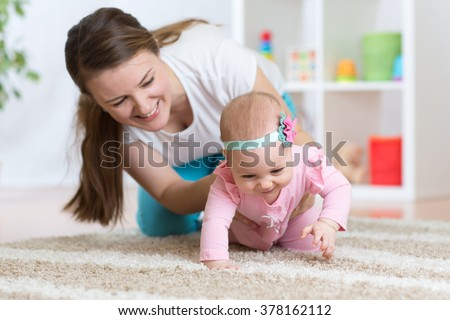 Funny crawling baby girl with mother - stock photo