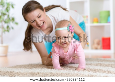 Funny crawling baby girl with mother at home - stock photo
