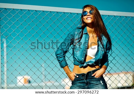 Funny crazy glamor stylish sexy smiling beautiful young woman model in  bright hipster summer casual jeans cloth  in the street behind blue sky - stock photo