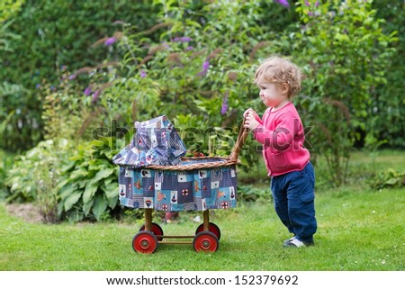 Funny curly baby girl playing with a vintage doll stroller in the garden - stock photo