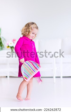 Funny curly little girl in a pink dress helping at home cleaning the floor sweeping in a white sunny living room