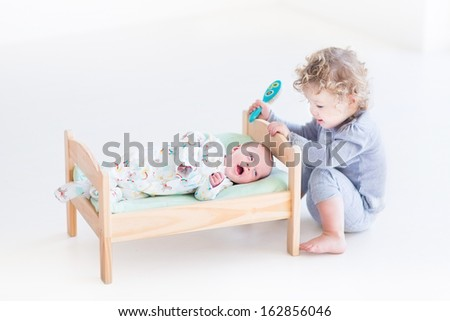 Funny curly toddler girl playing with hew newborn baby brother i - stock photo