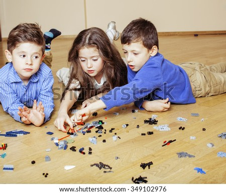 funny cute children playing lego at home, boys and girl smiling, first education role - stock photo