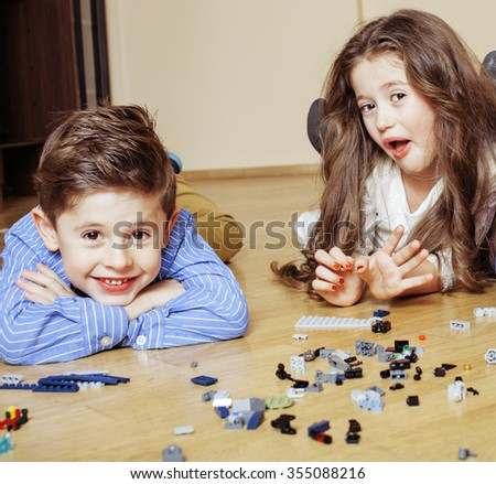 funny cute children playing lego at home, boys and girl smiling, first education role close up on floor - stock photo