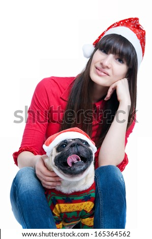 Funny cute friends pretty girl and her pug dog pet wearing red Santa Claus caps, having fun, smiling with toothy smiles, dog showing tongue, looking at camera. Isolated on white. Main focus on the dog - stock photo