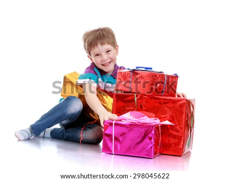 Funny cute little boy sitting on the floor and hugs the hands of a few beautifully packaged gifts that lie in boxes-Isolated on white