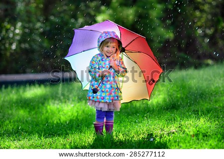 Funny cute toddler girl wearing waterproof coat with colorful umbrella playing in the garden by rainy and sunny day