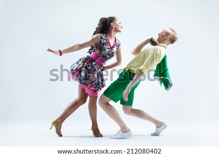 Funny dancer couple dressed in boogie-woogie rock'n'roll pin up style posing together in studio. Woman in yellow dress in black dots jokingly attack man in green shirt deviated from her. - stock photo