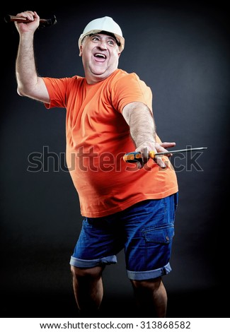 Funny dancing stout construction worker. Hands in the air. Helmet, hammer and screwdriver.  - stock photo