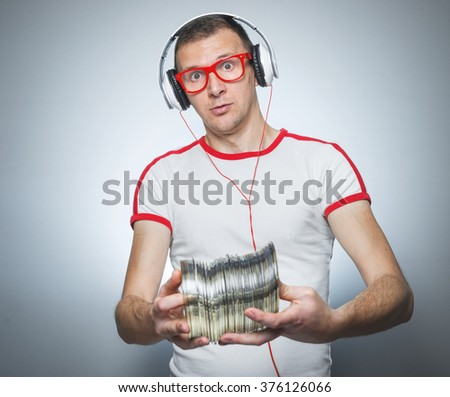 Funny dj holding a lot cds isolated on gray background. Close up party guy - stock photo