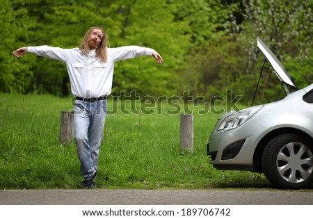 Funny driver praying a broken car by the road   - stock photo