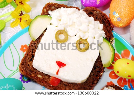funny easter sandwich with sheep head made from cottage cheese on dark bread as breakfast for child - stock photo