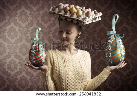 funny easter shoot of brunette female with yellow dress and bizarre hat with eggs in carton box . old fashion style - stock photo