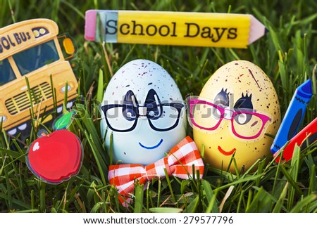 Funny eggs with American school objects on green grass  - stock photo