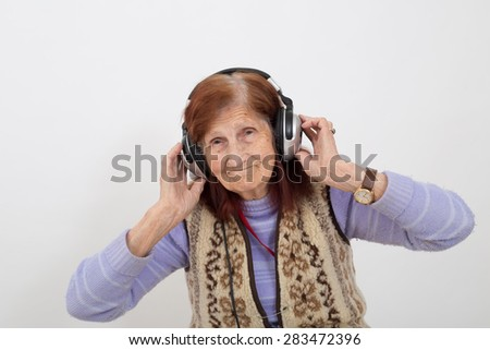 Funny Elderly lady listening music with headphones