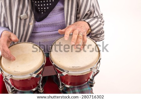 Funny elderly lady makes music with a wooden bongo. - stock photo