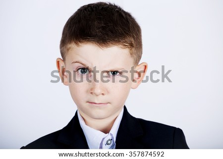 Funny emotion of  little boy young man with a raised eyebrow wearing costume with braces.Happy little boy over white background.Smiling, Happy, Joyful beautiful little boy , looking at camera. - stock photo