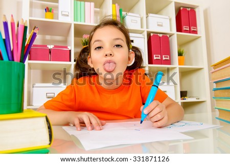 Funny emotional girl sitting at the desk with books and pencils and making her lessons. Education.