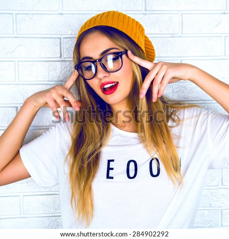 Funny emotions. Beautiful young blond haired woman in glasses and a yellow hat, making face, standing up against a light brick wall background - stock photo