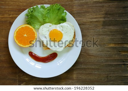 funny face serving breakfast, fried egg, toast and green salad - stock photo