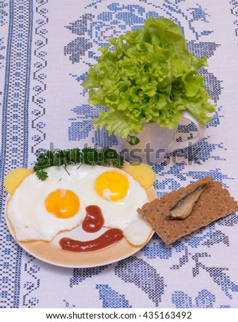 funny faces from eggs with cheese and sauce, lettuce and smoked herring - stock photo