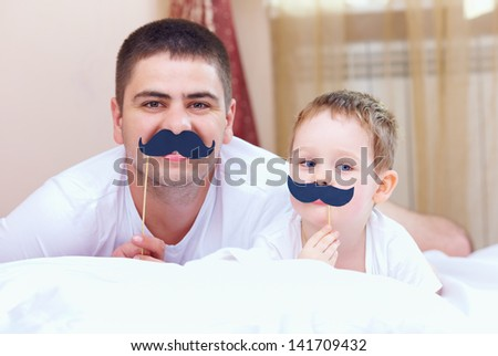 funny father and son with false mustaches, playing at home - stock photo