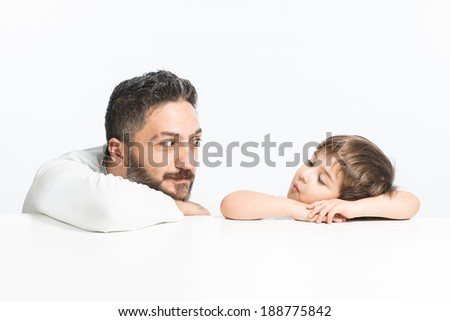 Funny father with funny expression for chheering up his son, both wearing white clothes - stock photo