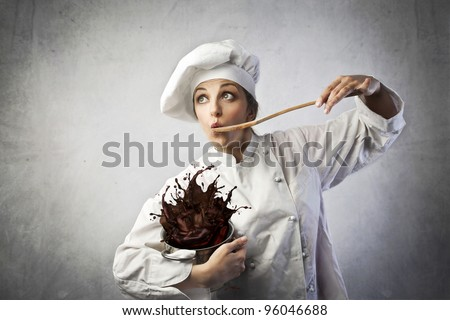 Funny female cook tasting some chocolate dough spilling from a pot - stock photo