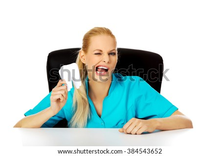 Funny female dentist sitting behing the desk and holding oversized tooth model - stock photo