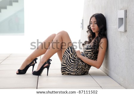 Funny female model at fashion with high heels sitting on the floor - stock photo