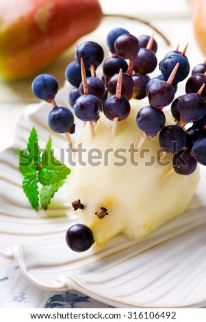Funny figure hedgehog  of fruit for children food, made by a child's hand.selective focus. - stock photo