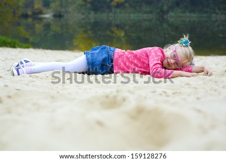 Funny five-year girl lies on the beach in autumn - stock photo