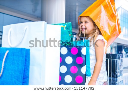 Funny girl among the pile of shopping bags - stock photo