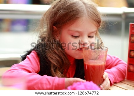 Funny girl at cafe indoor/Cute baby drinks tomato juice