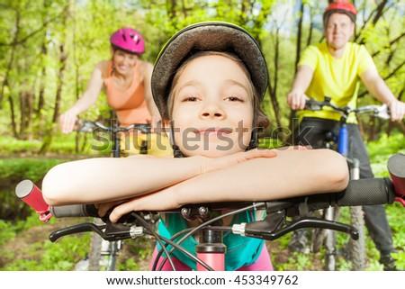 Funny girl bracing against handlebar of  the bike - stock photo