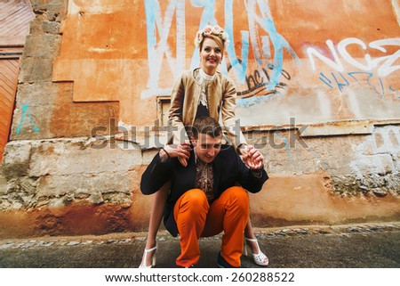 funny girl climbed to his boy on his shoulders - stock photo