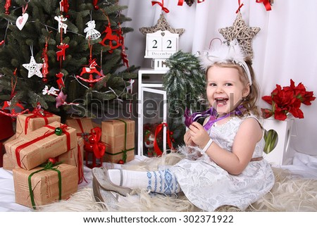 Funny girl in a white dress sitting near the Christmas tree among the gifts and toys