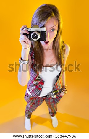 Funny girl in full growth with a camera in hand. Surprised by Samer looking at viewer. Isolation on a yellow background.