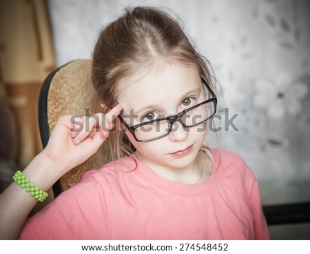Funny girl in glasses showing spinning finger to his temple. - stock photo
