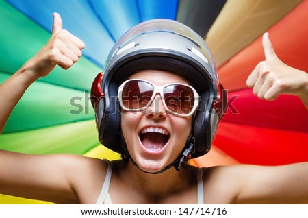 Funny girl in helmet having fun. Multicolored background. - stock photo