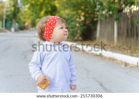 funny girl in red headband with biscuit - stock photo