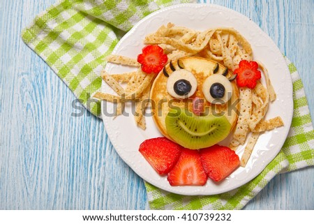 Funny girl pancake face with fruits and berries - stock photo