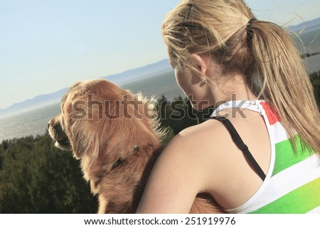 Funny girl plays with the dog outside - stock photo