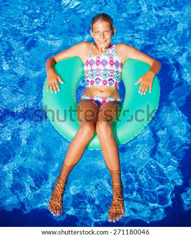 Funny girl swims in a pool in an green life preserver - stock photo