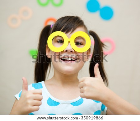 Funny girl with fake glasses. Happy child playing in home