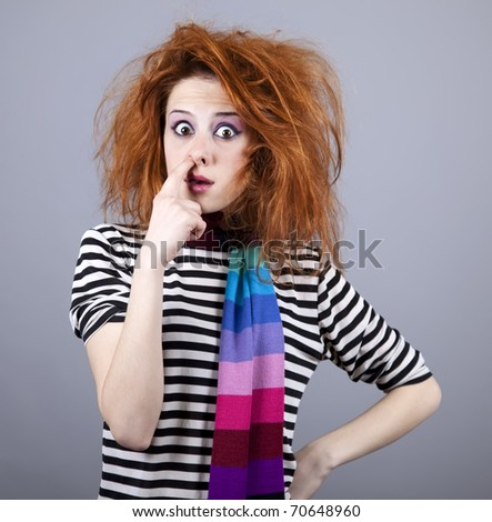 Funny girl with finger in nose. Studio shot. - stock photo