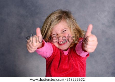 funny girl with thumbs up in front of gray background - stock photo