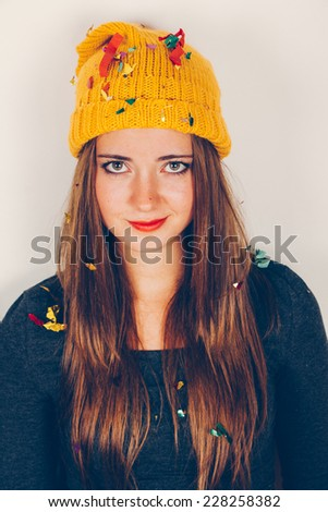 Funny girl with yellow wool cap in a boring party with confetti over head. Filter effect added. - stock photo